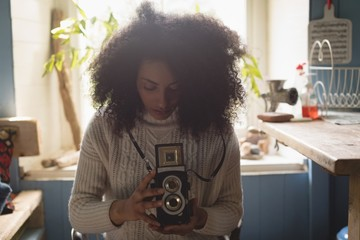 Woman looking at pictures on vintage camera at home
