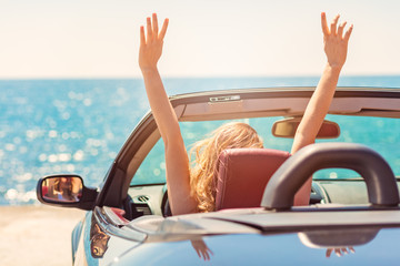 Happy and carefree woman in the car on the beach