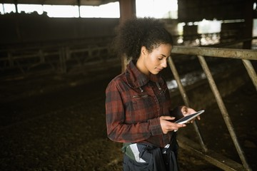 Female farmer using digital tablet in barn