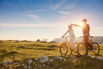 Biker couple with mountain bike pointing in distance at countryside Wall mural