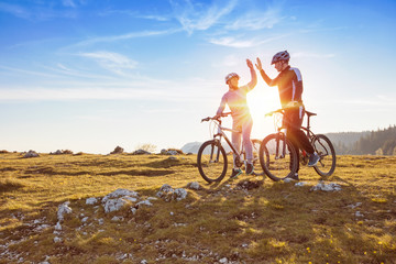 happy couple goes on a mountain asphalt road in the woods on bikes with helmets giving each other a high five Wall mural