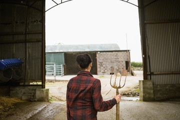 Rear view of woman standing with garden fork