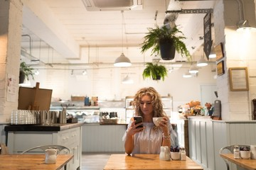 Woman using phone while holding coffee cup