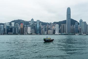 hong kong skyline with sailing boat under cloudy sky,china.