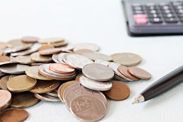 Business, finance, saving money, banking, loan, investment, taxes or accounting concept : Coins, pen and calculator on office desk table