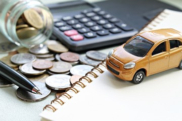 Business, finance, saving money, banking or car loan concept : Miniature car model, calculator, coins scattered from glass jar, notebook paper and pen on office desk table