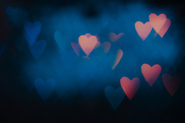 Abstract background of colorful hearts on black backdrop. Bokeh of defocused glitters, blurred blue and pink symbols of love. Festive wallpaper of holidays and celebrations, St. Valentine's day
