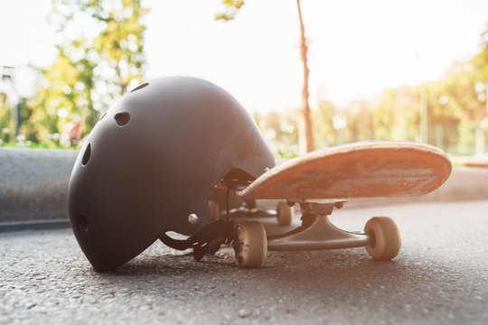 Close up skateboard and helmet, sport equipment. Summer extreme sport challenge and training background, protective sportswear in competition