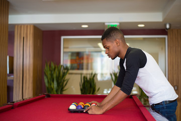Closeup portrait, young man hanging out, playing billiards at red pool table, isolated indoors background