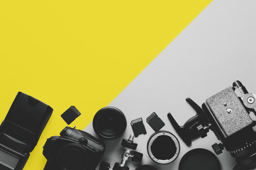 Digital camera, lenses and equipment of the photographer on a grey background
