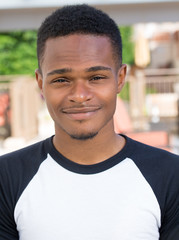 Closeup headshot portrait of fine young man, undergrad student, smiling, isolated on outside outdoors background. Customer satisfaction guarantee