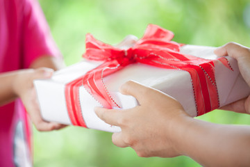 Hands of parent giving Christmas gift to child girl on green nature background. Christmas concept.