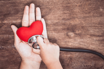 Red heart on woman's hand and little child girl examines the heart with doctor's stethoscope on wooden background. Healthcare medical  concept
