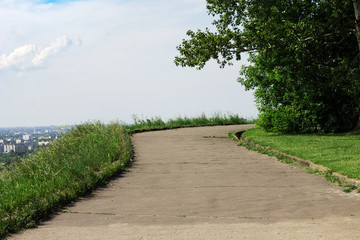 The footpath in the Park. The road leads to the top. Summer landscape.