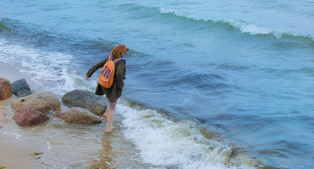 a woman stands with her feet in the cold sea water