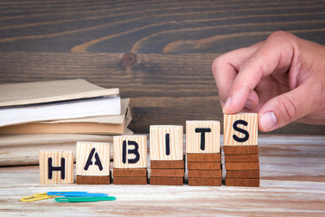 Habits concept. Wooden letters on the office desk, informative and communication background.