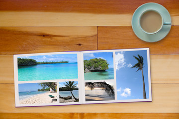 Photobook Album on Wooden Floor Table with Travel Photos and Coffee or Tea in Cup