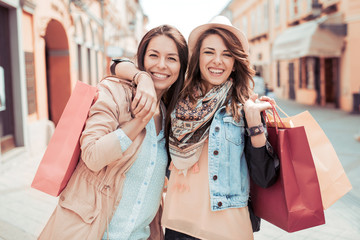 Two young womens outdoors with shopping bags.