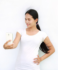 Asian girl taking pictures of herself through cell phone on white background.