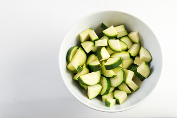 sliced zucchini, prepared vegetables in a white bowl on a light gray background, copy space, top view from above