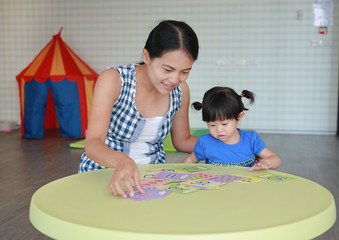 Asian Child girl and mother playing flash card for Right Brain Development at the playroom.