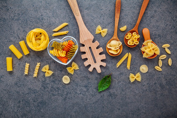 Italian foods concept and menu design. Various kind of Pasta Farfalle, Pasta A Riso, Orecchiette Pugliesi, Gnocco Sardo and Farfalle in wooden spoons setup on stone background with flat lay.