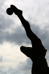 silhouette statue kick volleyball against cloud sky, rattan ball.