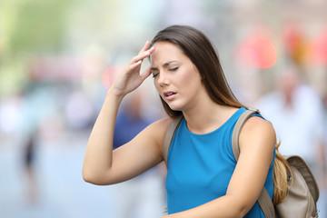 Woman suffering headache outdoor in the street