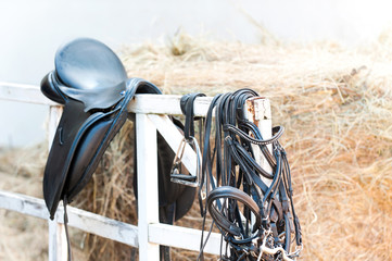 Keuken foto achterwand Paardrijden Black leather equestrian sport equipment and accessories hanging on fence