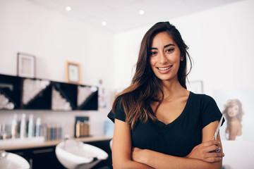 Female hairdresser standing in salon Wall mural