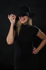 Young happy woman portrait of a confident businesswoman showing by hands on a black background. Ideal for banners, registration forms, presentation, landings, presenting concept
