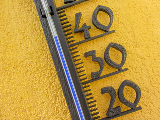 thermometer in yellow wall measuring external air temperature over forty celsius degrees