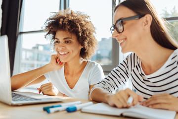 Positive female students enjoying distance learning