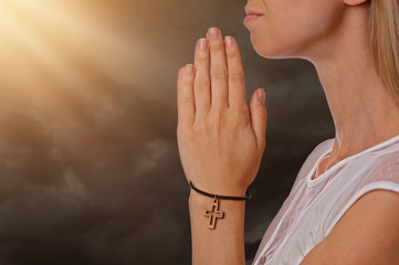 Woman praying holding christian cross on hand, faith, religion concept
