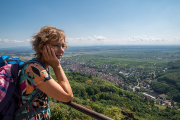 A short break at a vantage point in France; woman looks at Ribeauville in the Vosges