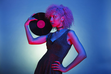 millennial black woman with groovy hair holding an old eighties vinyl with retro disco lights