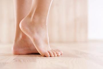 Zdrowa stopa dziecka.  Stopy  bosego dziecka na tle drewnianej podłogi