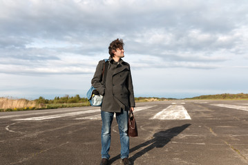 Young man in blue jeans and grey coat standing on the runway going on vacation on air plane with brown leather bag in hand. White aircraft on the background