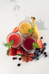 Assortment of bright fruit and berry smoothies on white table. Summer refreshing drinks. Space for text