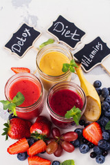Assortment of bright fruit and berry smoothies on white table. Summer refreshing drinks. Detox or diet concept