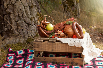 picnic - cured meat, sausages in a basket on the blanket