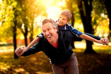 Composite image of father giving his son piggyback ride