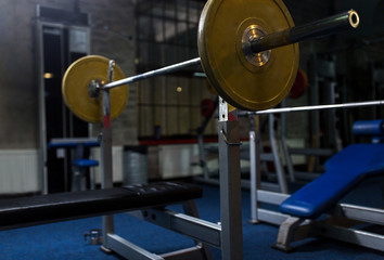 weight bench with barbell in gym
