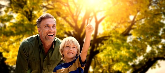 Composite image of boy pointing in the air with his father
