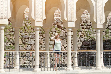 Girl in a hat standing among columns. Sunny day