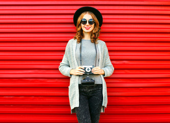 Fashion autumn portrait smiling woman holds retro camera on a red background