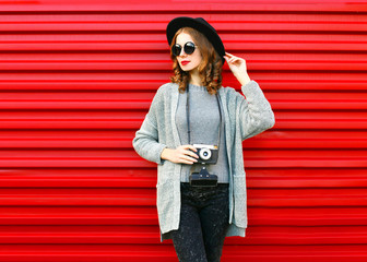 Fashion autumn portrait woman holds retro camera on a red background
