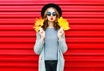 Fashion autumn portrait woman with yellow maple leaves on a red background Wall mural