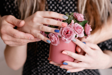 Man and woman holding roses in crimson cup together. Sensitive concept of gift with love, romantic proposal, close relationship between people