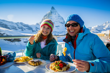 Wall Mural - Swiss fondue dinner family skiers enjoying break for lunch, mountain view Matterhorn, Switzerland.